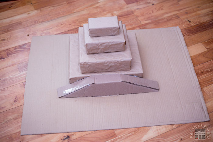 Hot glue cardboard piece to front of ziggurat