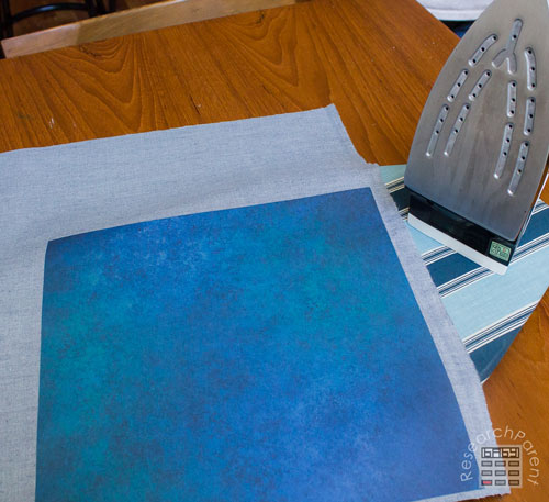 Iron scrapbook paper onto iron-on adhesive.