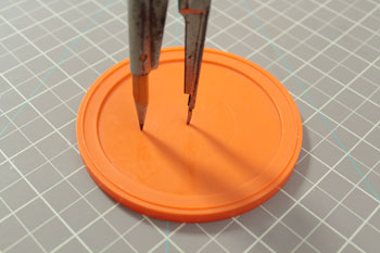 Drawing circle on lid with compass.